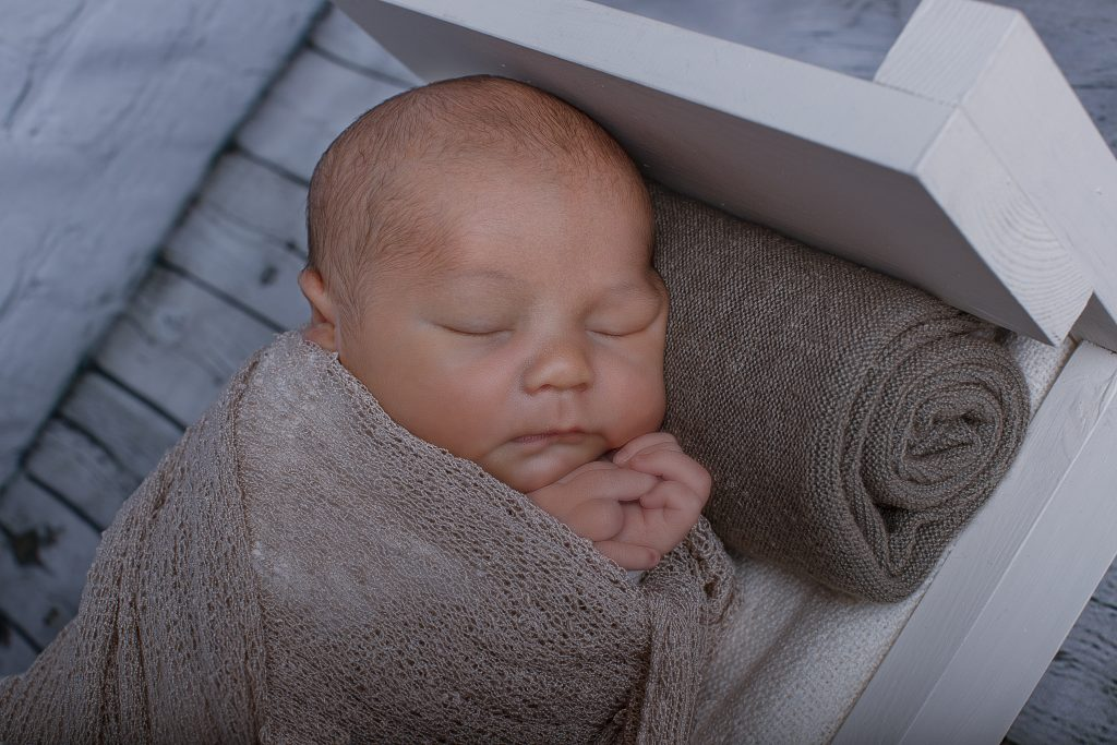 newborn baby on bed photography